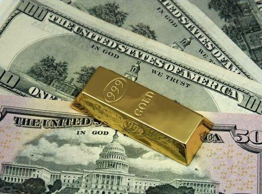 слиток золота на долларах
